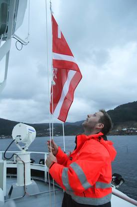Kaptein Erling Lorentzen fra NFT heiser rederiflagget etter overleveringen. Foto: Havyard Group AS