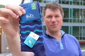 Disse sokkene Øistein Aleksandersen viser fram er laget av gammelt utrangert utstyr fra oppdrettsnæringen. Foto: Designia - Lars Antonsen.
