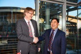 Jefe ejecutivo de Nordlaks, Inge Berg, dandose la mano con el ejecutivo de CIMC Raffles, Li Minggao, luego de cerrar el trato para construir dos Havfarms. Foto: Edvard Kristiansen