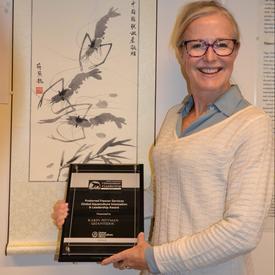 Professor Karin Pittman viser stolt frem prisen hun mottok i Kina. Foto: Magnus Petersen.