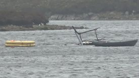 The helicopter could be seen upside down and partially submerged in the loch. Photo: BBC