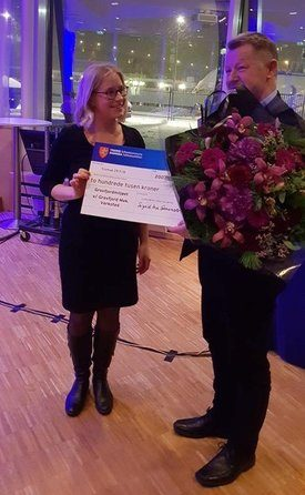 Her får daglig leder i GMV, Bård Meek-Hansen overlevert blomster og sjekken på to hundre tusen kroner av fylkesråd for kultur og næring i Tromsø, Sigrid Ina Simonsen. Foto: GMV.
