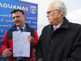 El director regional de Aduanas, Pablo Elvenberg, con el intendente de la región de Los Lagos, Harry Jürgensen, mostrando la certificación de origen del producto de Salmones Camanchaca.