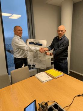 Roger Halsebakk (t.v) fra Sølvtrans og Halvard Aas fra Aas Mek tar hverandre i hånden under kontraktinngåelsen. Foto: Aas Mek.