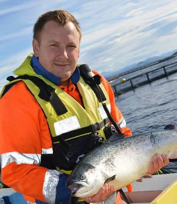 Lokalitetsleder Arve Mohn Haug har aldri angret på at han takket ja til tilbudet om jobb på sjøen. Her er han avbildet med en flott laks på merdkanten. Foto: Emilsen Fisk
