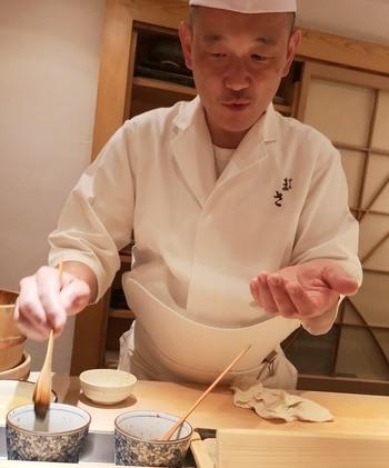 Sushi-chef Masakatsu Oka  gir et lite penselstrøk som siste finish på fisken før han overleverer en av de over seksti bitene. Foto: Ole Andreas Drønen.