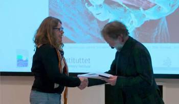 Edgar Brun fra Veterinærinstituttet overleverer Fiskehelserapporten 2019 til Friede Andersen i Mattilsynet. Skjermdump fra Veterinærinstituttet.