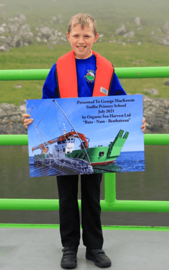 George MacKenzie, 8, with the commemorative poster presented on board the Bàta nam Bràthairean by OSH co-founder Alister MacKinnon. Click on image to enlarge. Photo: OSH.