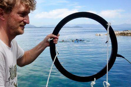 Daniel Nyqvist held opp ein ring som skal ligge rundt eit grøngyltereir. På ringen festar ein antenner, kamera og mikrofon, og informasjonen som blir sanka inn skal seinare koplast mot avanserte algoritmar. Foto: Torhild Dahl/HI.