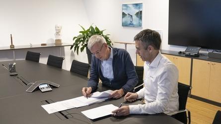 CEO i Bakkafrost Regin Jacobsen, og CEO i Nofitech, Robert Hundstad signerer avtalen. Foto: Bakkafrost
