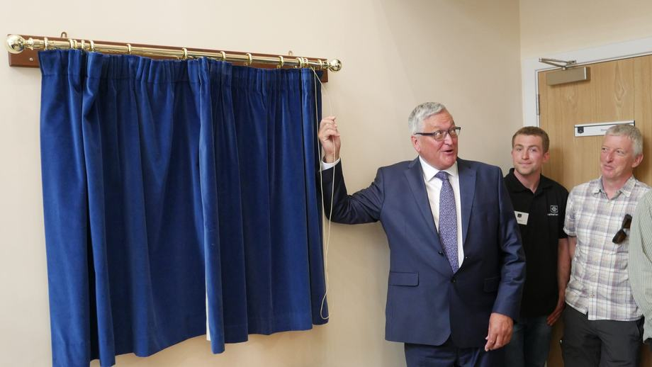 <p>Cabinet Secretary Fergus Ewing prepares to open the curtains concealing a plaque marking the opening of the hatchery.</p>