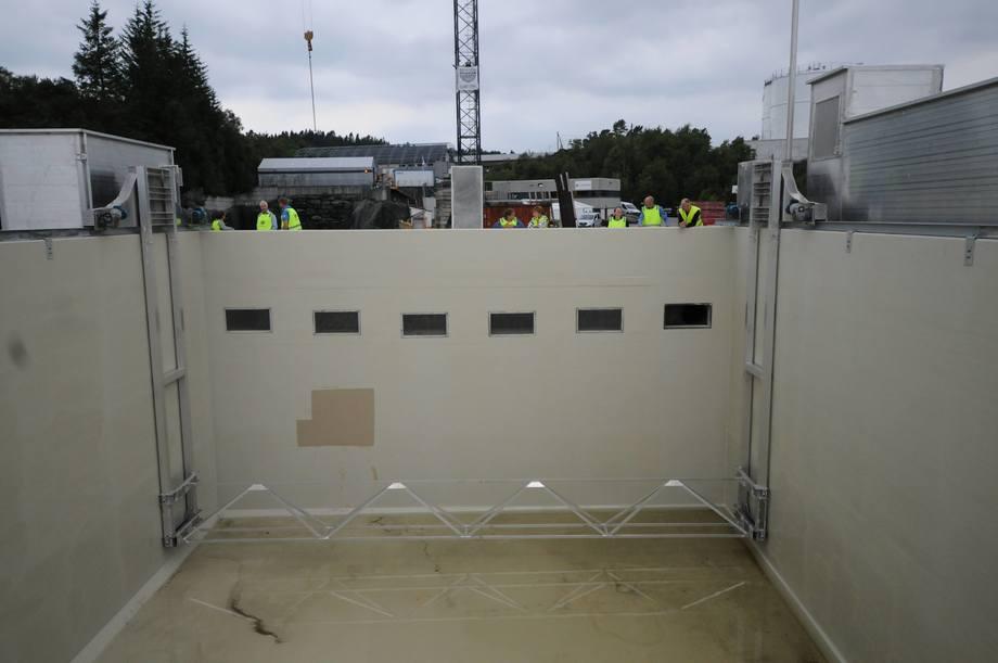 <p>Vannet går ut gjennom åpningen oppe på veggen. Under kan man se feste for vaskeroboten som skal holde merden ren og hente ut slam. Foto: Pål Mugaas Jensen/Kyst.no</p>