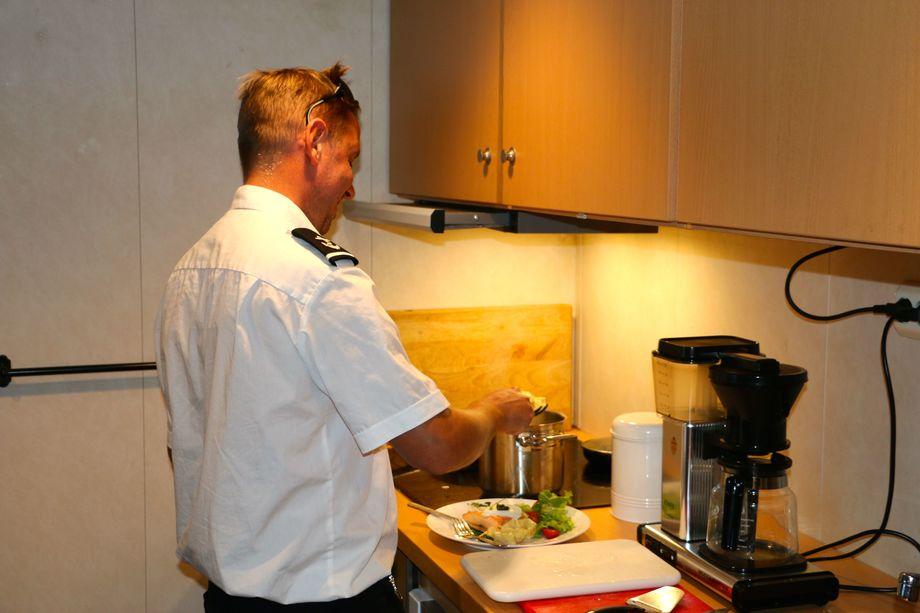 <p>Matros Raymond Hestnes lager maten sin selv, her laks og pasta. Foto: Andrea Bærland</p>