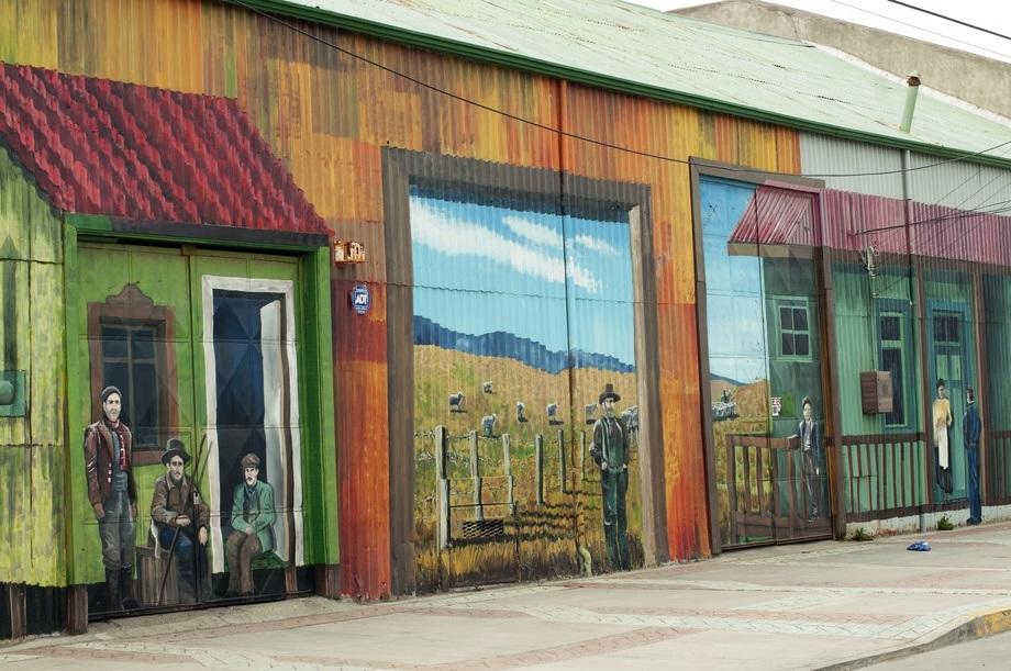 <p>Murals brighten up the streets between grey brick buildings.</p>