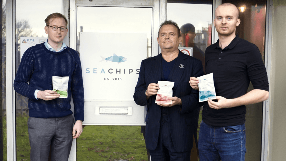 From left: Dominic Smith, Jonathan Brown and Daniel Pawson with packets of Sea Chips. Smith and Pawson are now launching their own branded smoked salmon produced at Brown's Maryport smokery. Photo: Sea Chips.