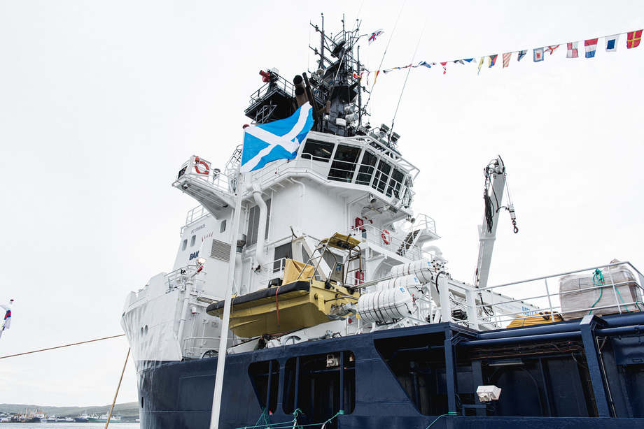 <p>A Saltire flies on a flag pole in front of the MS Bakkanes, while a Faroese flag is mounted above the bridge. Photo: Bakkafrost.</p>