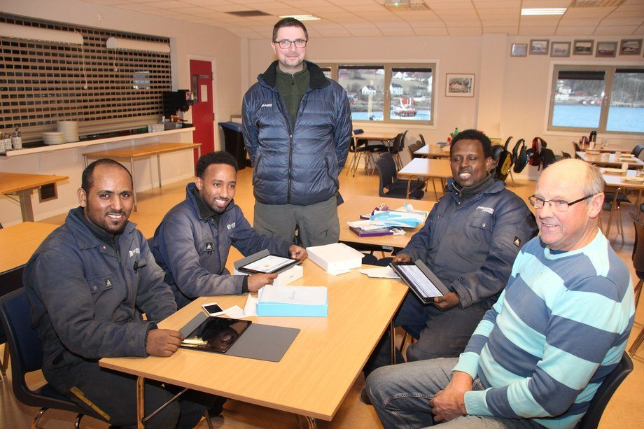 Amanual Fishaye (til venstre), Mahad Ali, Anders By og Siyad Mohammed ønskes velkommen til Moen Marin Service av «husnestor» Alv Homo. Foto: Moen Marin.