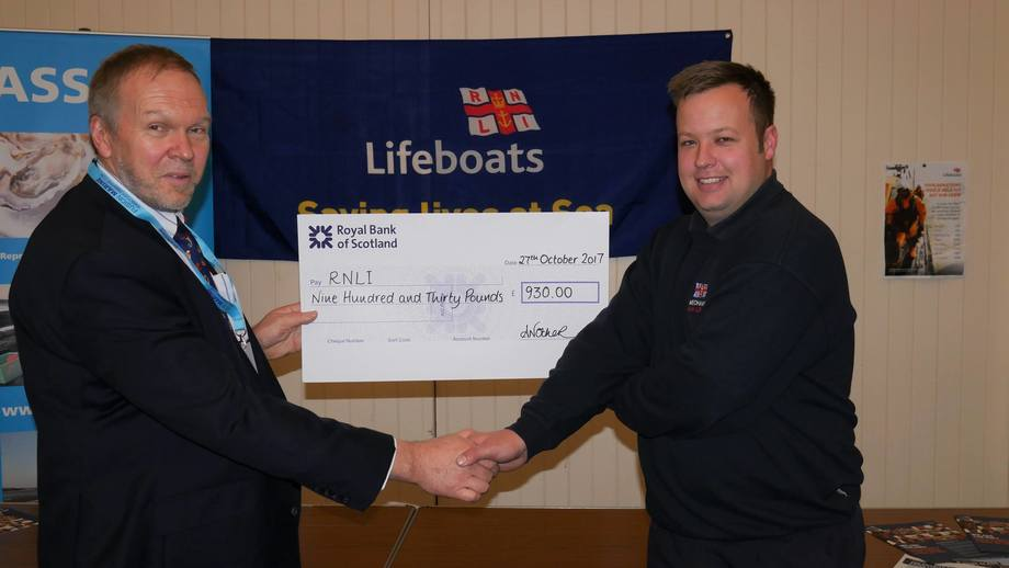 Nick Lake, chief executive of the ASSG, presents RNLI lifeboat mechanic Tom Kennedy with a cheque for £930. Photo: Gareth Moore/FFE