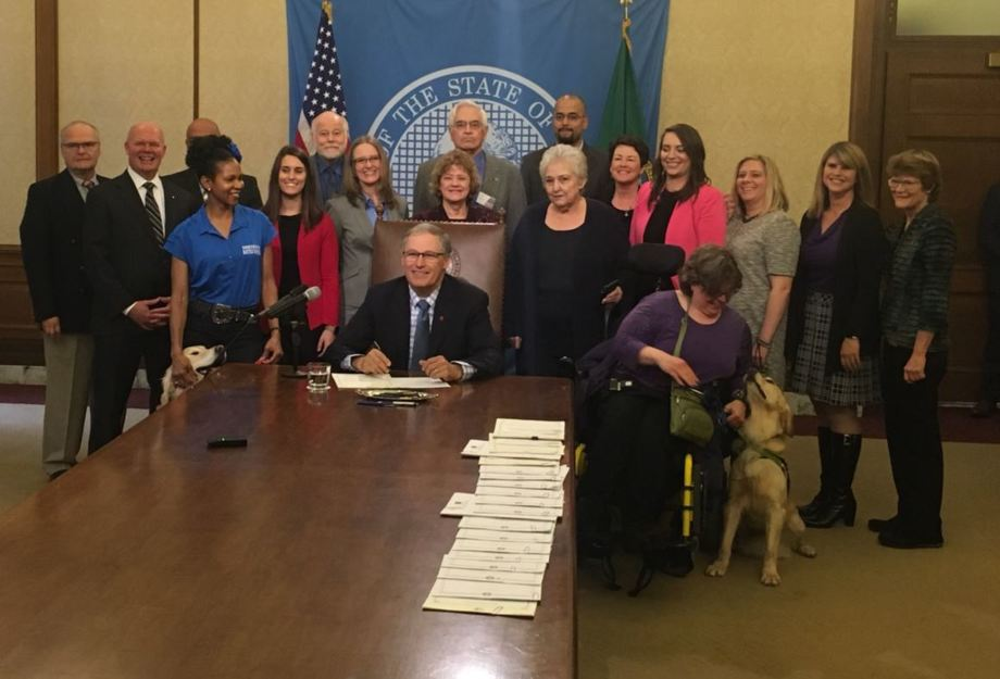 Jay Inslee signs a number of bills into law, including phasing out non-native fish farms, setting standards for service animals, and increasing awareness for bone marrow donation, on Thursday. Photo: Twitter