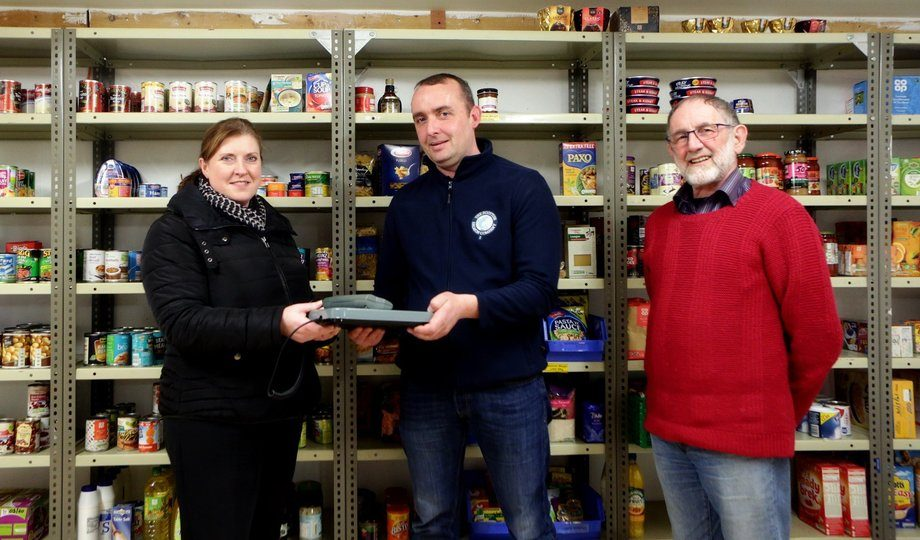 SSC's Robert Currie presents food bank volunteers Katie Walker and Gavin Elliott with new scales. Photo: SSC.