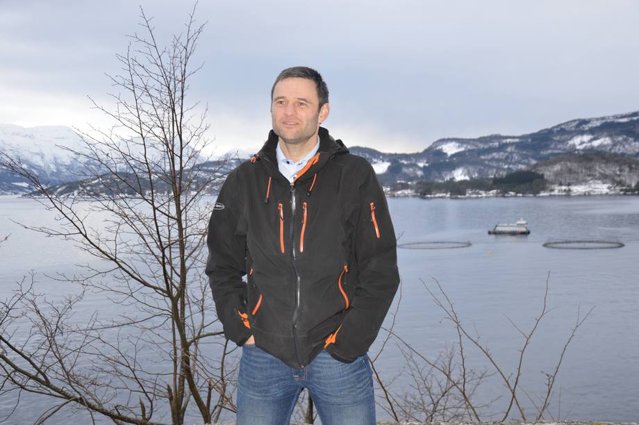 Erlend Haugarvoll, daglig leder i Lingalaks. Bak han kan man se fôrflåten «Aud», i Saltkjelen, der fisken har blitt fôret på marine algeoljer siden oktober 2018.  Foto: Ole Andreas Drønen
