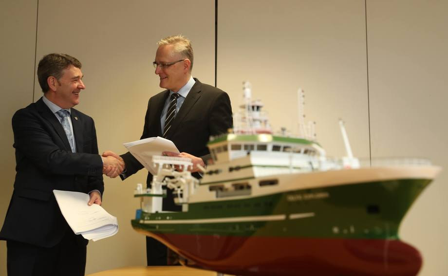 Dr Peter Heffernan, CEO Marine Institute og Hans Ove Holmøy, CEO Skipsteknisk AS markerer signeringen av kontrakten. I forgrunnen forskningsskipet «Celtic Explorer» som Skipsteknisk tidligere har designet for Marine Institute. Foto: Skipsteknisk.