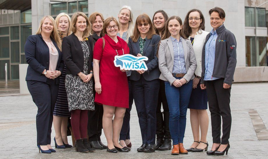 SAIC chief Heather Jones, left, and Rowena Hoare, senior researcher at the IoA, hold the WiSA logo as women working in Scottish aquaculture celebrate the launch of the organisation outside the Scottish Parliament. Photo: WiSA.
