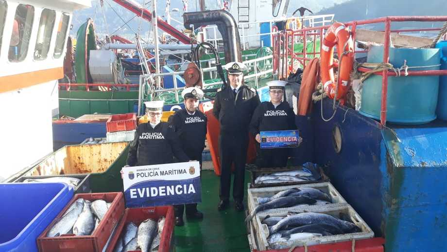 Navy personnel next to some of the seized salmon. Photo: Chilean Navy.