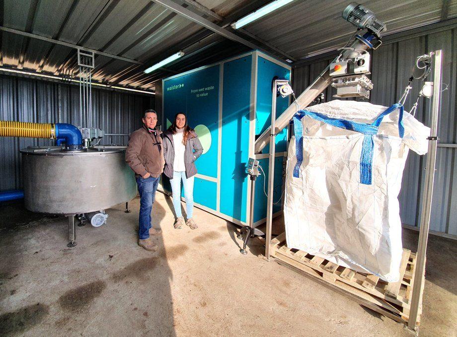 Felice Borlini, jefe de operaciones de Waister y la fundadora de Circular Solutions, Maite Navarro, junto con la máquina secadora instalada en piscicultura de Salmonífera Dalcahue. Foto: Circular Solutions.