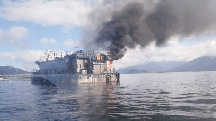 The feed barge on fire at Mowi's Isolte Abel salmon farm in Chile. Photo: Sur Informa.