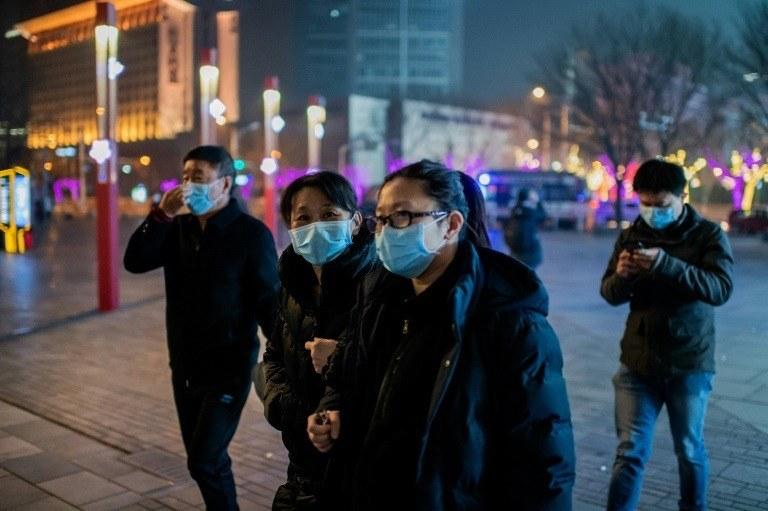 Personas caminando por la zona de Sanlitun, en Pekín, con mascarillas protectoras por Coronavirus. Foto: Agencia AFP.