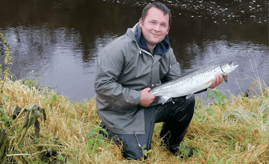 An angler with a farmed salmon caught on the river Girvan. Photo: Girvan Mains Fishing Club.