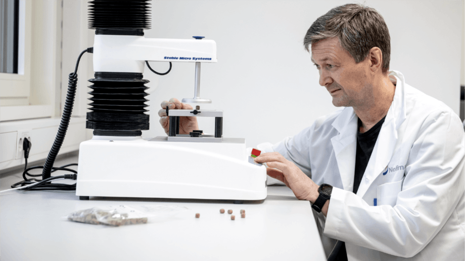 Tor Andreas Samuelsen measures the feed pellets' fracture strength (hardness). Photo: Helge Skodvin©Nofima.