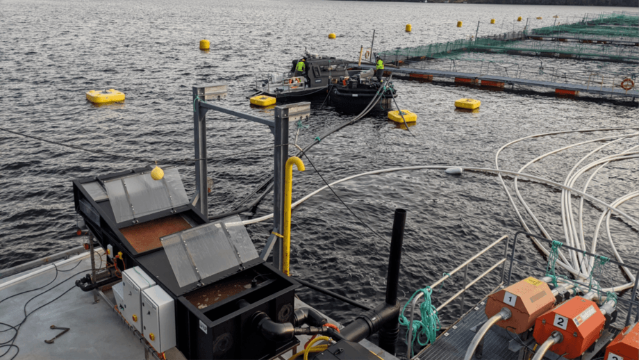 Part of the Lift Up sludge collection in place at a Lerøy salmon farm in Norway. A belt filter is seen in the foreground, and the floating sludge collection tank is seen in front of the salmon pens. Photo: Lift Up.