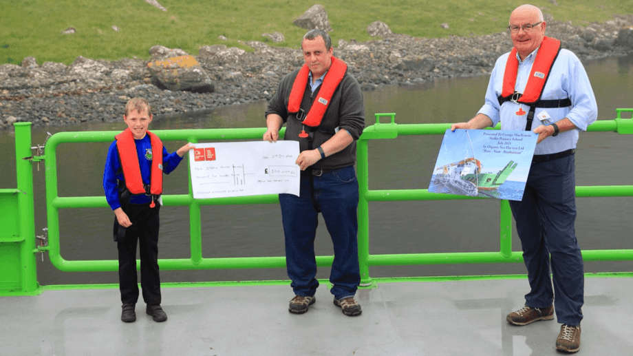 Staffin Primary School pupil George MacKenzie receives a £500 cheque for his school from OSH chief operating oficer Robert Wyvill. OSH co-founder Alister MacKinnon, right, presentedGeorge with a commemorative poster. Photo: OSH.