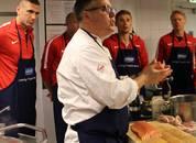 <p>Fredrik Hald, kokk i Ler&oslash;y forklarer og l&aelig;rer brannspillerne gode m&aring;ter &aring; tilberede laks p&aring;. Foto: Ler&oslash;y</p>