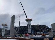 <p>A crane lifts a side panel into position.</p>