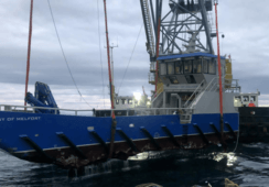 Sunken workboat lifted on to salvage ship